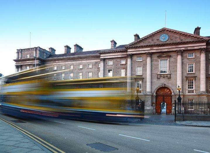 Front entrance to Trinity College Dublin with buses going past.