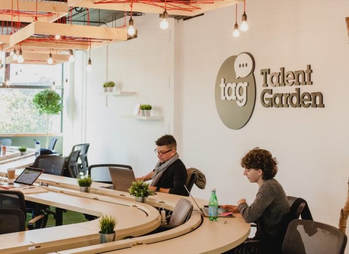 A man and a woman working in a bright co-working space. The Talent Garden logo is on the wall behind them.