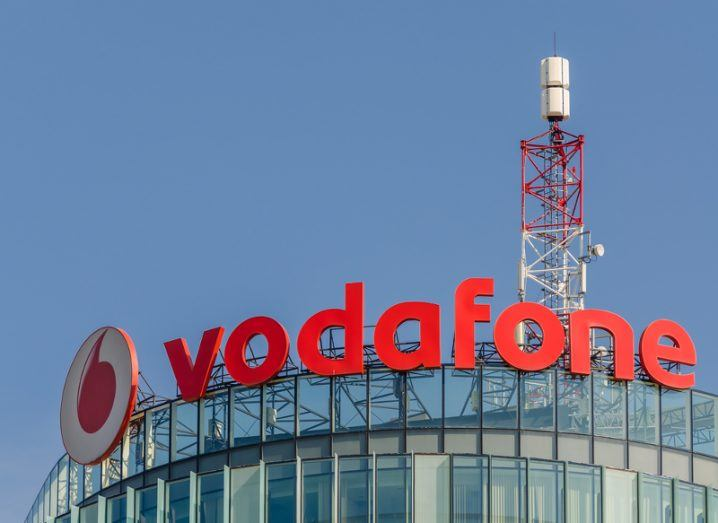Image of a Vodafone building with a cell tower on the roof under a blue sky.