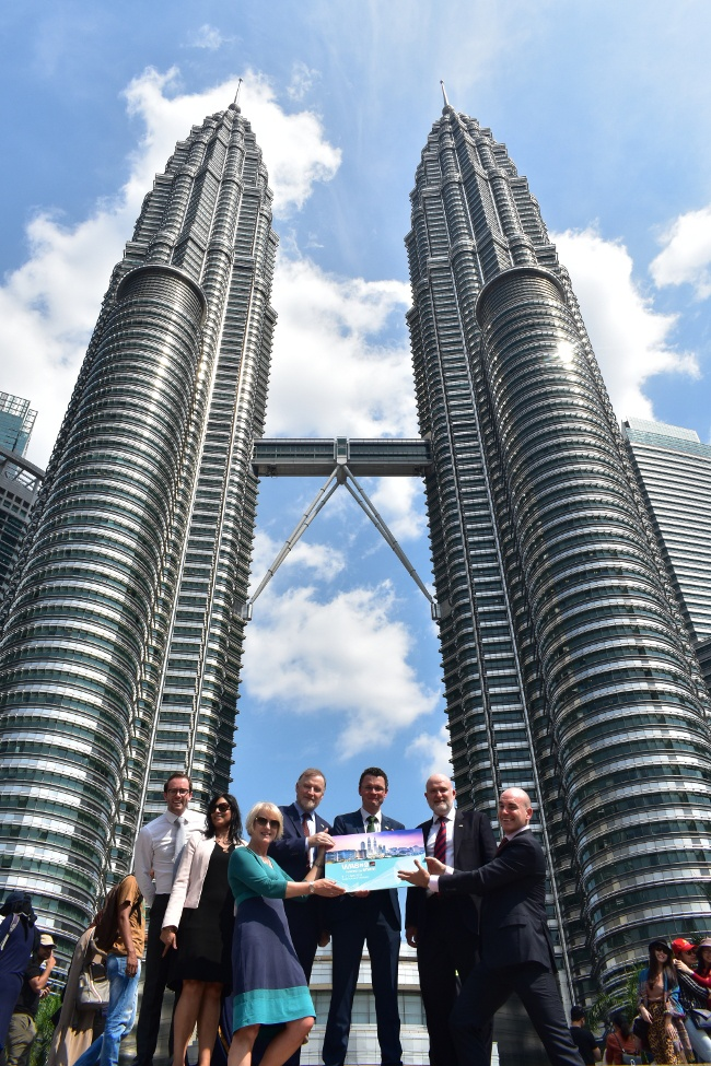 Group of people stand before two towering buildings in the heart of Kuala Lumpur.