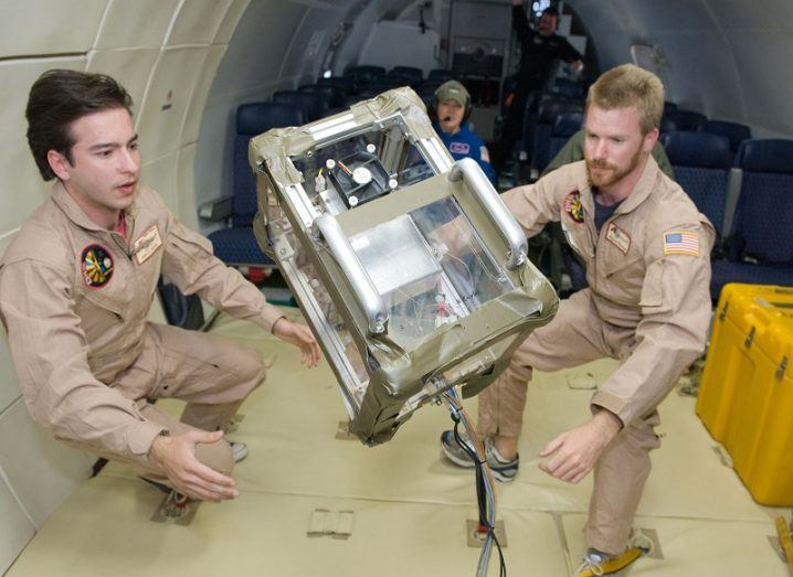 Two male researchers in beige astronaut outfits looking at an experiment in zero gravity.