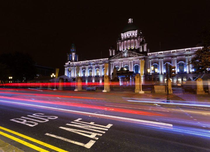 Traffic lights streak past Belfast City Hall at night.