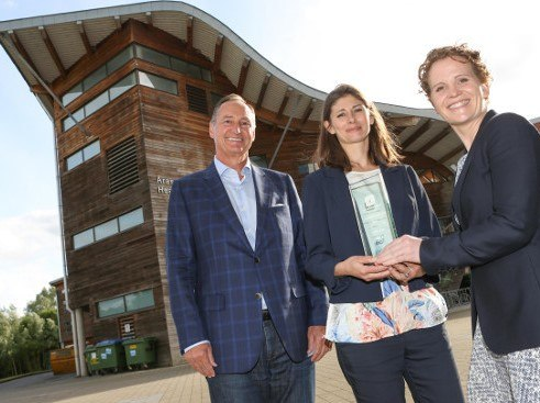 A man in blue checkered suit stands with two women holding a prize in front of a modern building.