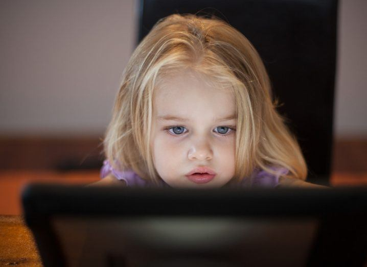 A young girl with blonde hair and blue eyes looks at a computer screen.