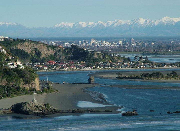 Panoramic view of Christchurch, New Zealand from the sea with mountains behind the city.