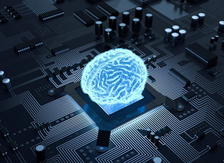 Image of a blue fluorescent brain on top of a CPU on a computer circuit board.