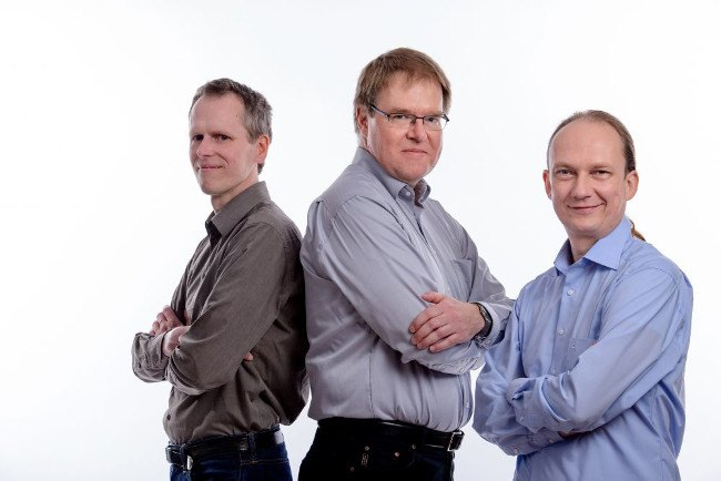 Three men in grey and blue shirts stand with their arms folded.