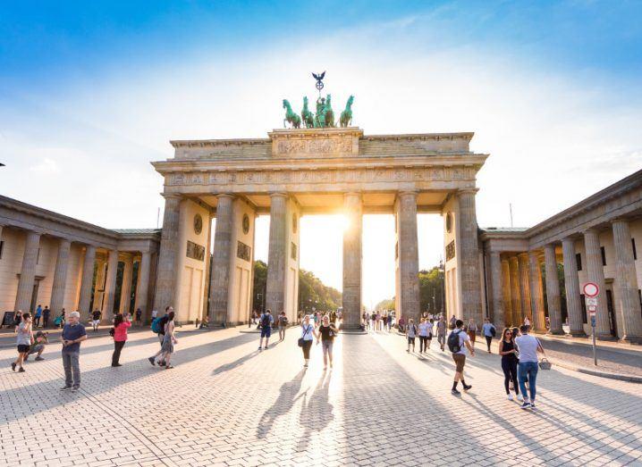Sunlight flows through Germany's Brandenburg Gate in Berlin in a courtyard with columns.