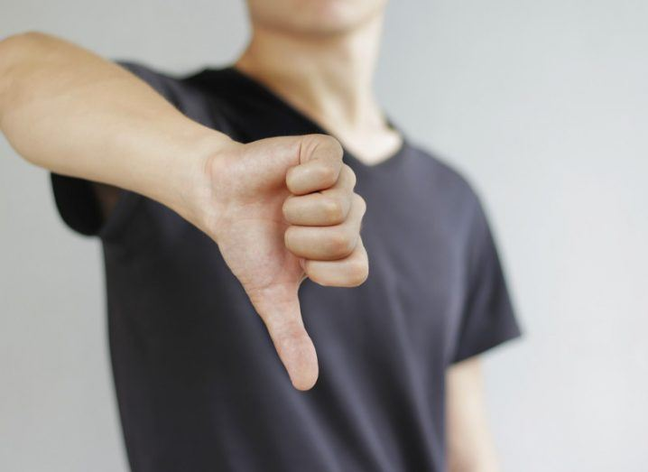 Young man in black t shirt showing a sign of dislike with thumb down.