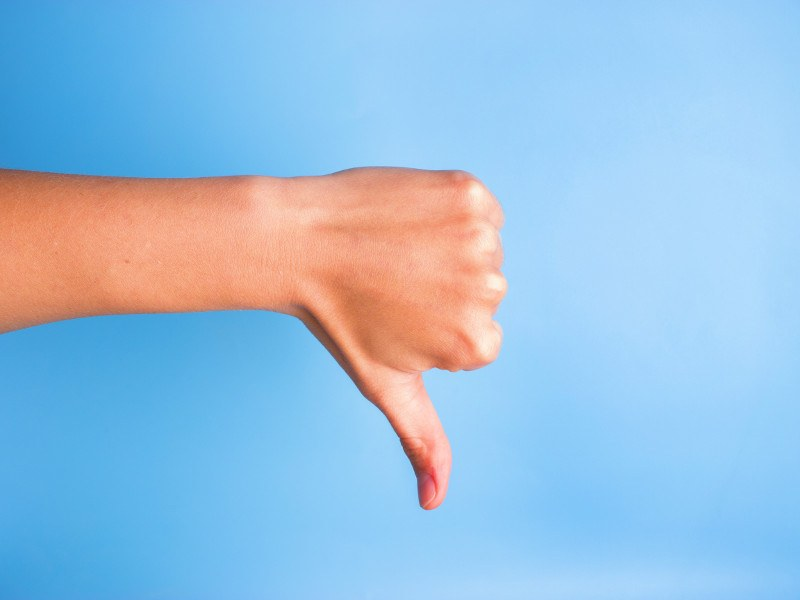 Close-up of woman's hand gesturing thumbs down against blue background, indicating another bad scandal at Facebook.