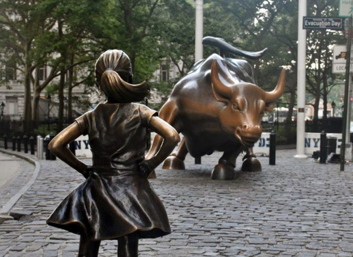 Fearless girl statue in front of charging bull on Wall Street, New York.