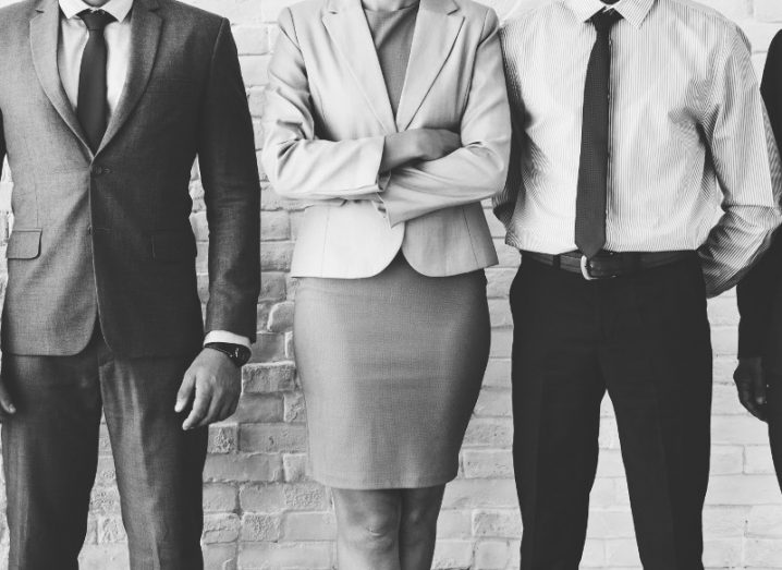 Black and white image showing a woman standing between two men, indicating the gender divide in entrepreneurship.