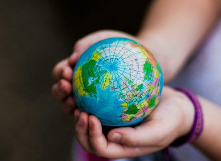 A child holds a mini globe in her hands.