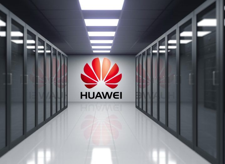 Huawei logo on the back wall of dark server room with glass doors either side.