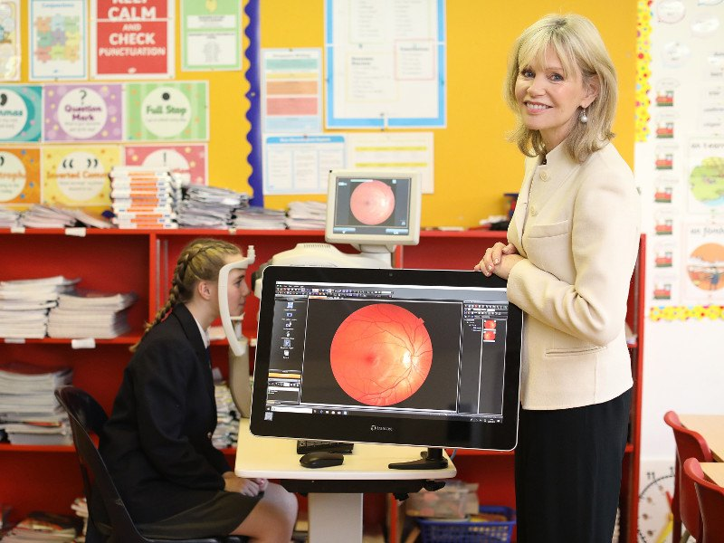 Woman with blonde hair and beige jacket stands beside a computer screen while a young student has her eyes scanned.