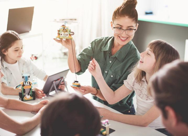 A woman teaches a class mostly of girls about robotics.