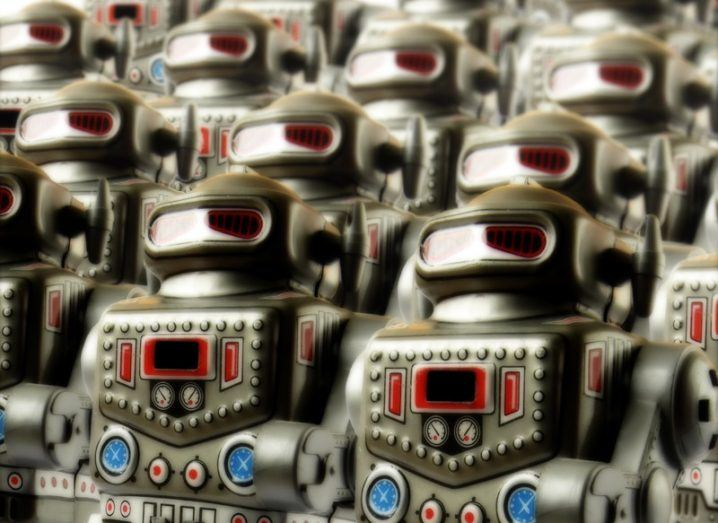 Ranks of grey robots with red visors for eyes.