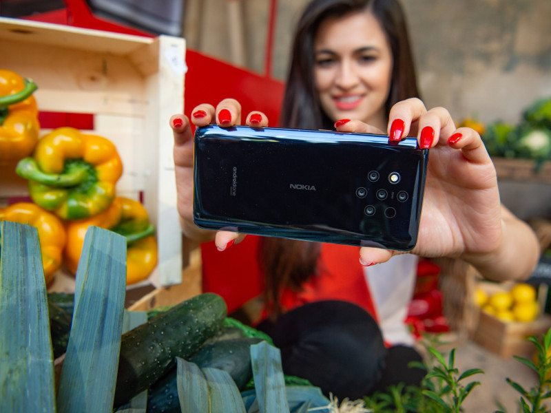 Woman in red jumper takes picture of plants using the new Nokia 9 Pureview with five cameras.
