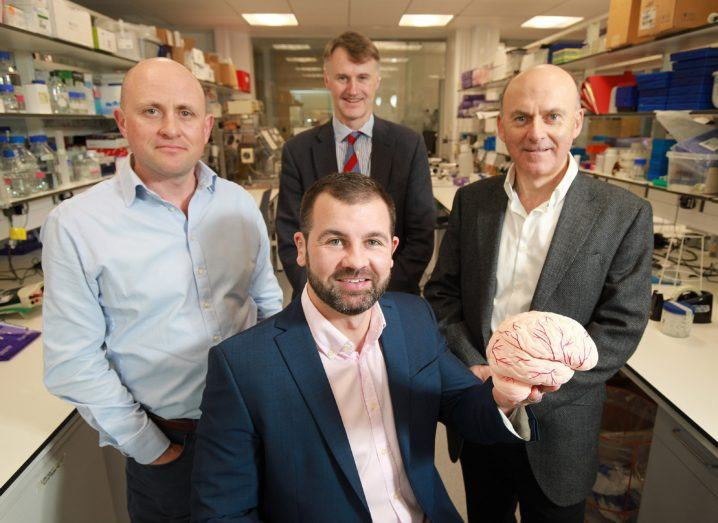 Four men in a research lab, one is sitting and holds up a model of the human brain.