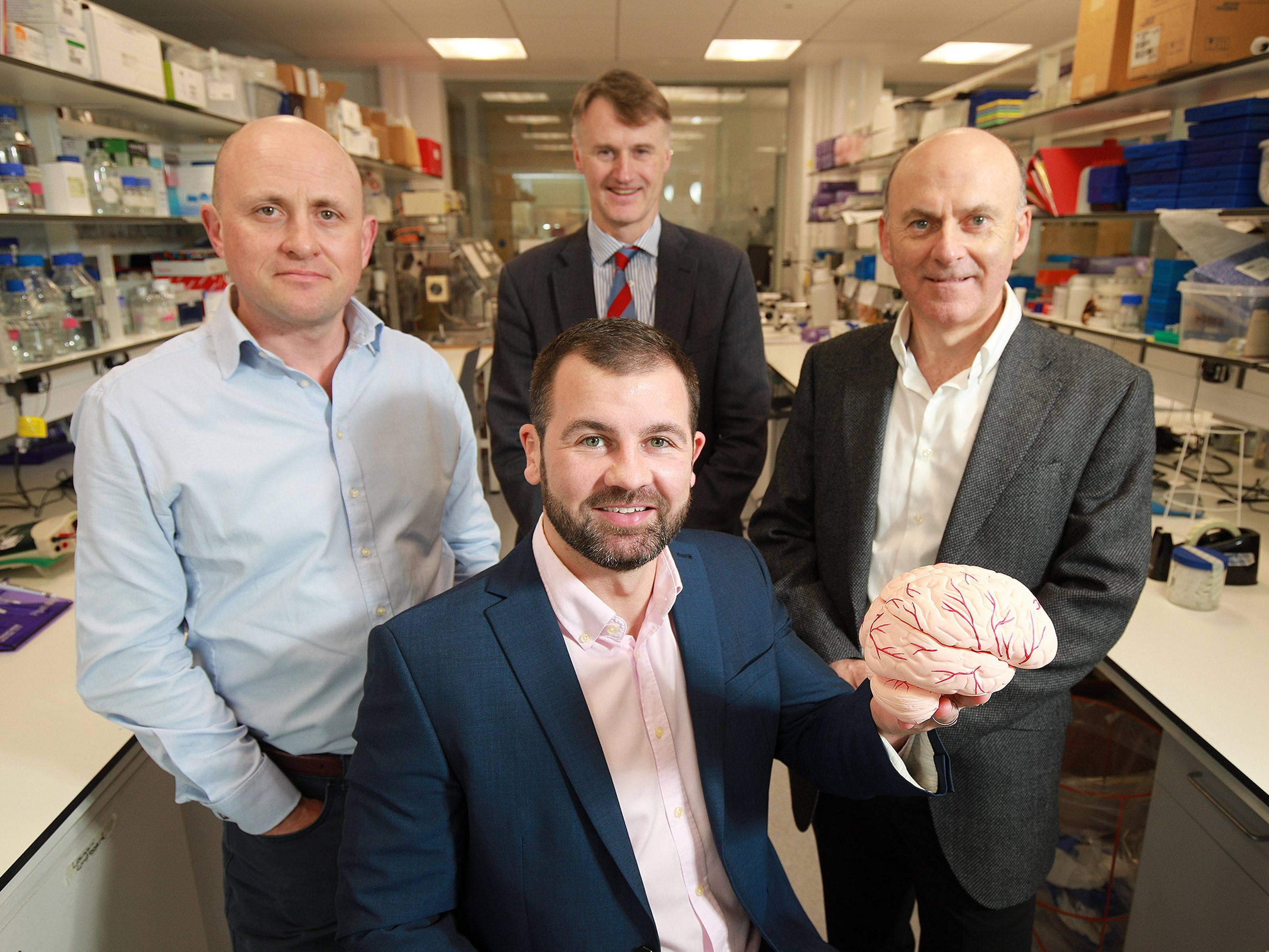 Four men in a research lab while man who is sitting holds up a model of the human brain.