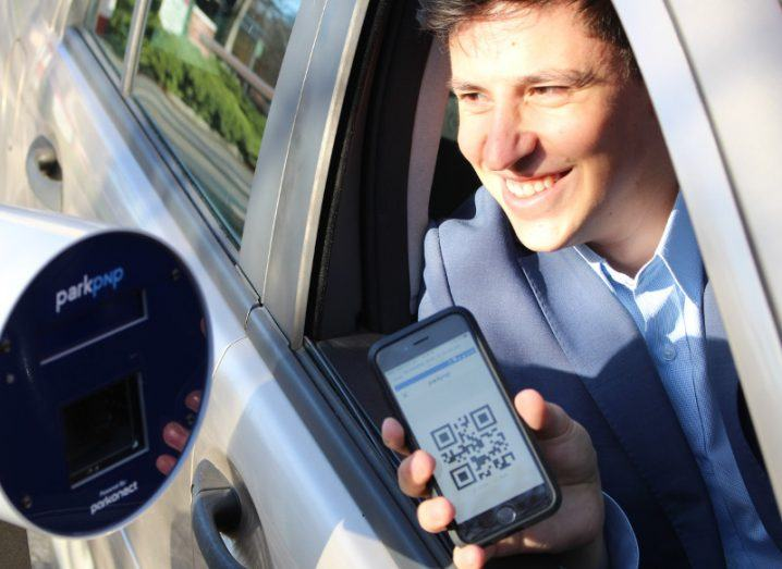 Dark haired man in car holds phone with QR code up to sensor.