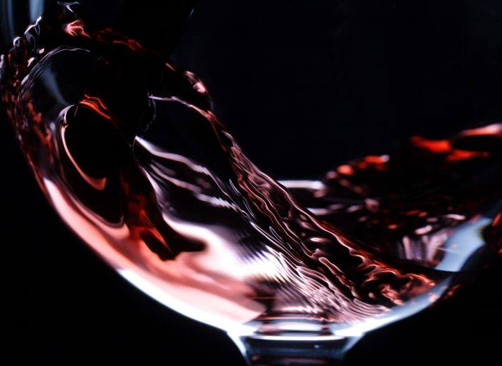 Close-up of red wine pouring in a glass isolated on black background.