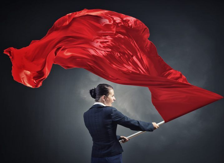Young determined businesswoman with red flag in hands, symbolising revolution.