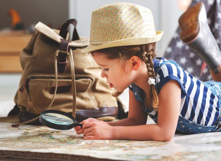 little girl in pigtails wearing straw hat and looking at a map through a magnifying glass.