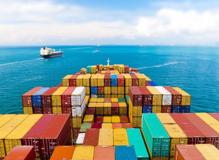A giant cargo ship festooned with colourful shipping containers sets out on an ocean voyage over a blue sea.