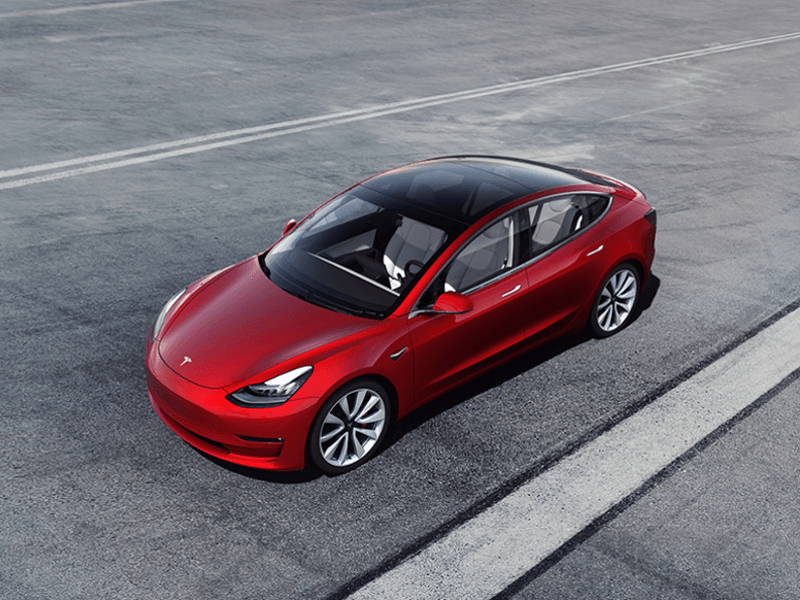 Picture of a red Tesla Model 3 on a grey asphalt surface.