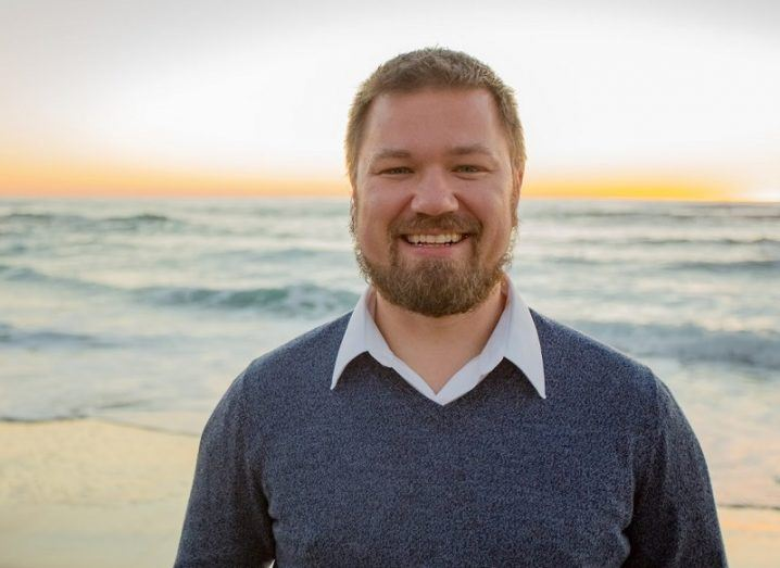 Erik Trask smiling in a light blue jumper on the beach at dusk.