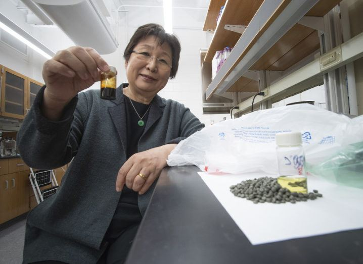 A woman sits at a lab bench beside a small mound of pellets, a container of gasoline-like fuel and a plastic bag. She holds a small container of dark oil produced through recycling plastic.