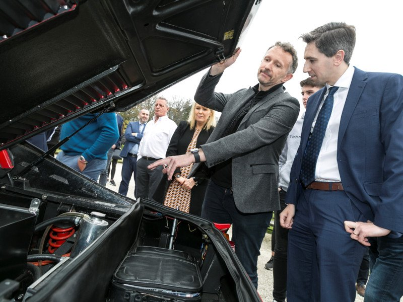Two men look under the hood of a Ferrari.