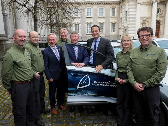 Seven men and one woman stand beside a new electric vehicle outside Irish government buildings.