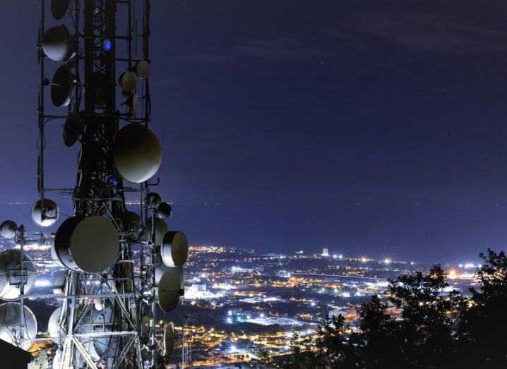 Cell tower overlooking a city of lights at night.