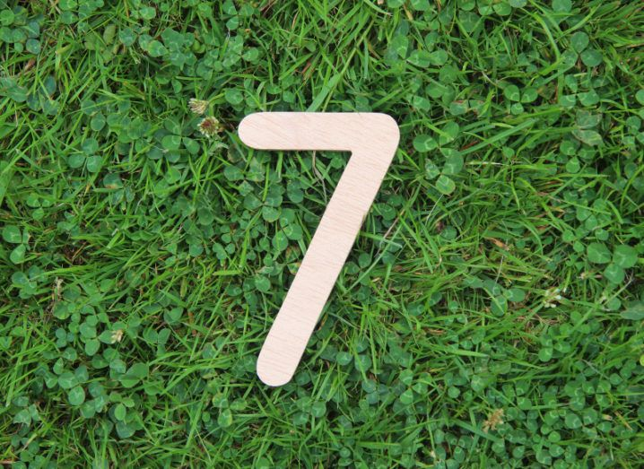 A light wooden number seven placed on a field of grass and shamrocks.
