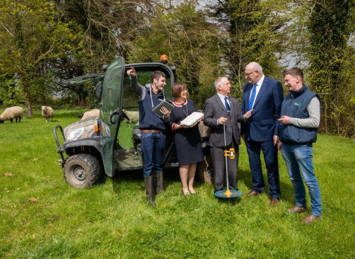 Group of people standing in front of a tractor and holding wireless broadband equipment in a field.