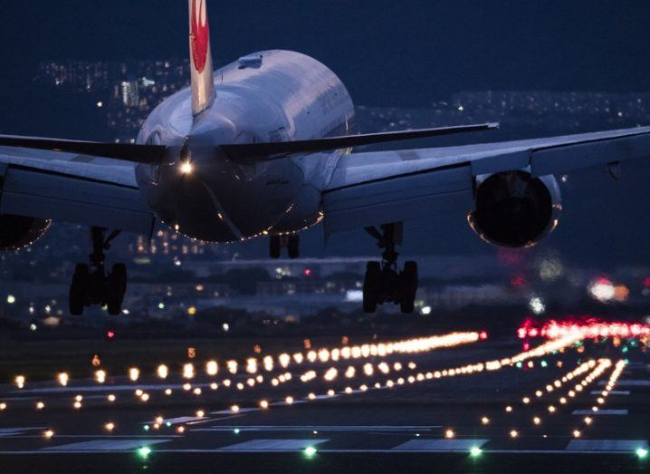 Rear view of a commercial jetliner landing at night at an airport runway lit up by landing lights.
