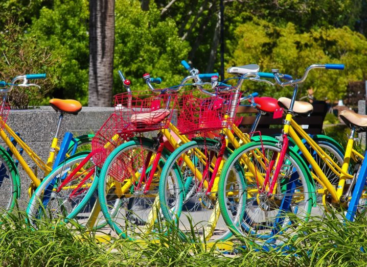 A number of brightly coloured Google bicycles lined up on a meadow.