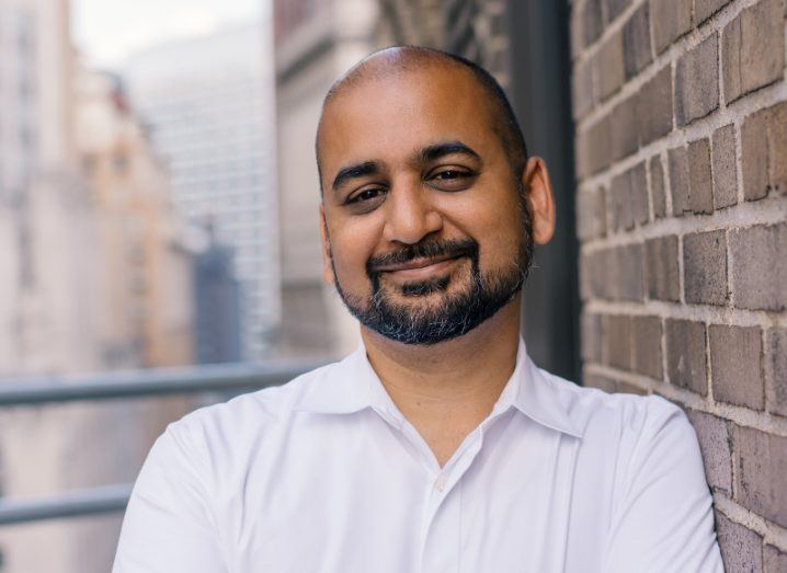 Anil Dash smiles with his arms folded as he leans against a red brick wall.