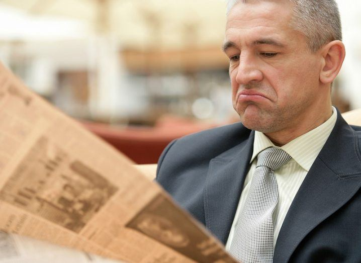 Man in a suit and tie unimpressed at reading an April Fool's story in a newspaper.