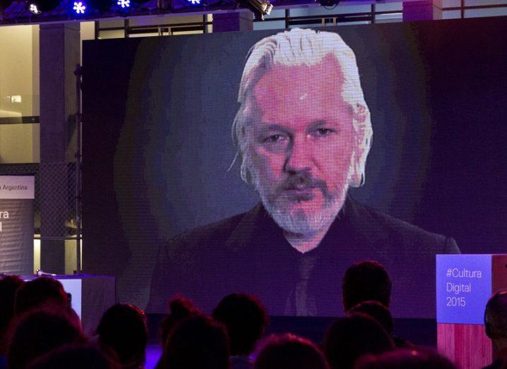 A darkened conference room with a video feed of Julian Assange taking part in a livestreamed interview.