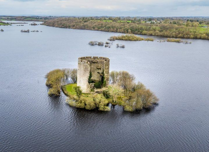An ancient castle on a small island in a large lake.