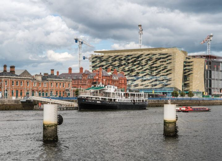 Central Bank of Ireland on Dublin's quays with old buildings and a boat in front of it.
