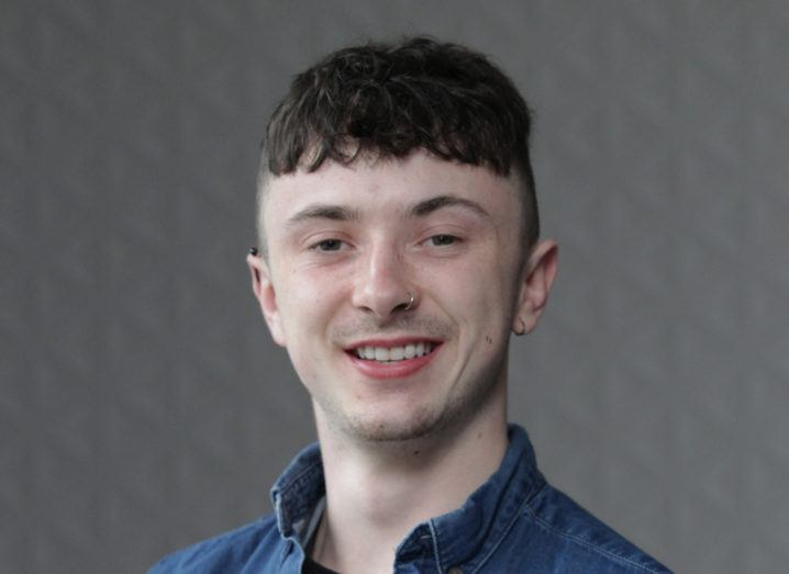 Headshot of Chris Barrett, a smiling young man with a nose piercing in a denim shirt.