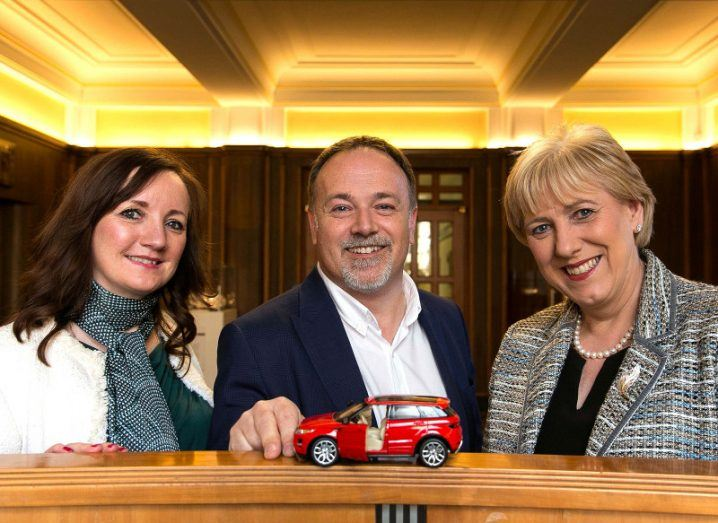 Two women and a man with a model of a red car.