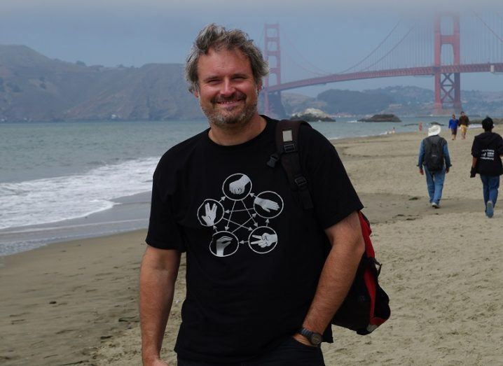 Dominic Zerulla in a black t-shirt smiling on a beach with the Golden Gate Bridge in the background.