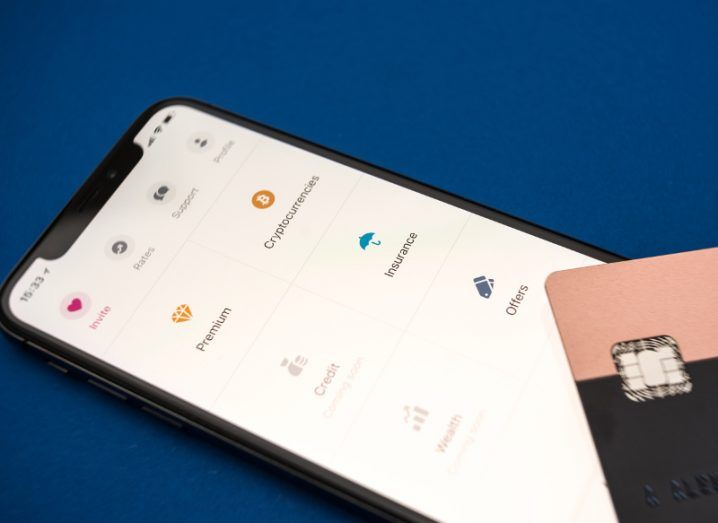 Close-up of Revolut card sitting on top of a smartphone currently open in the Revolut app.