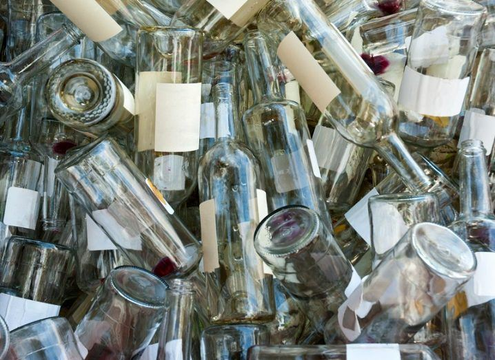 A large pile of empty, clear wine bottles.