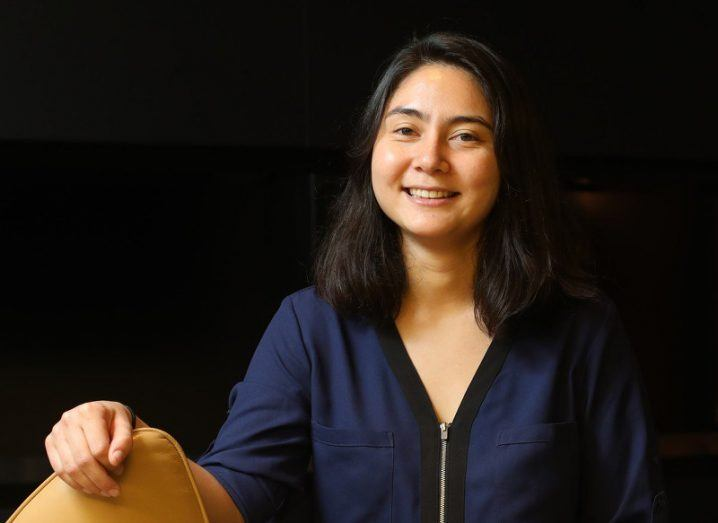 Erika Cheung smiles in a dark room where she is sitting comfortably, looking directly at the camera.